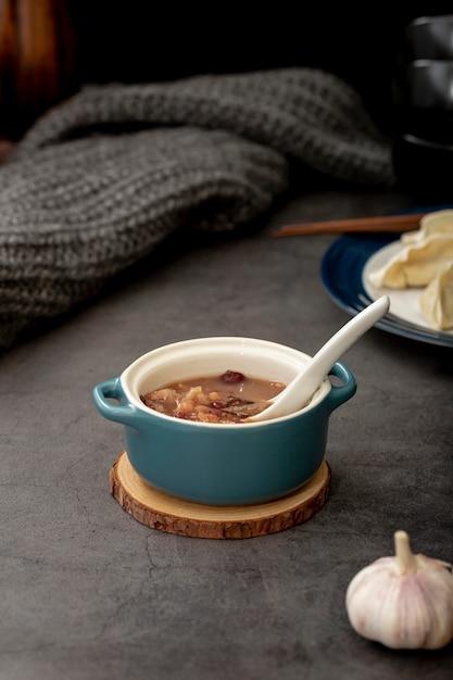 Sopa de frijoles en un frasco azul con ajo sobre un fondo gris Foto gratis