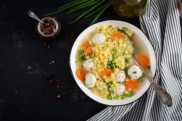 Sopa italiana de albóndigas y pasta sin gluten stelline en un tazón sobre la mesa negra. Foto gratis