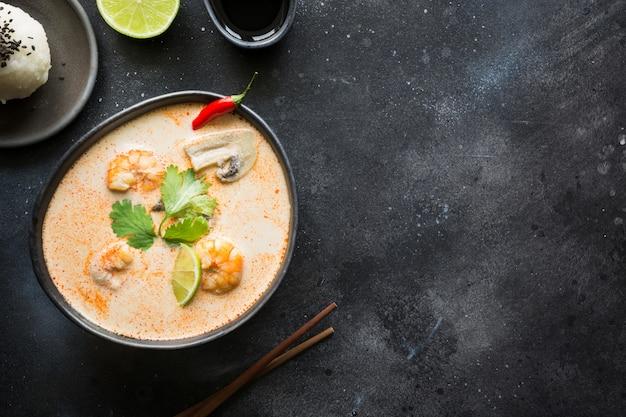 Sopa picante tailandesa de tom yam kung con camarones, mariscos, leche de coco, ají y arroz. Foto Premium