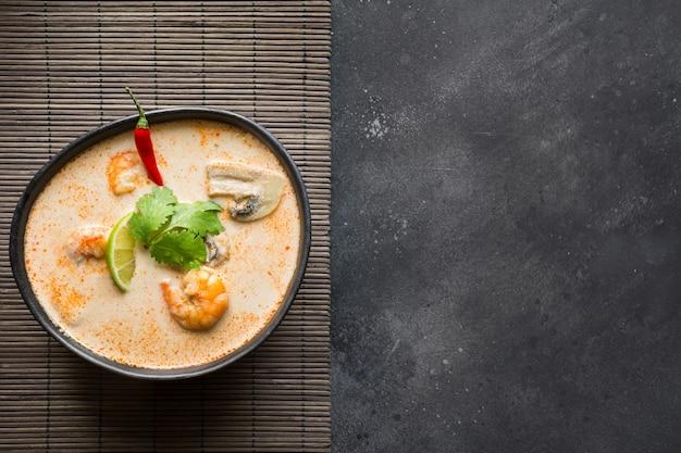 Sopa picante tailandesa de tom yam kung con camarones, mariscos, leche de coco y ají. copia espacio Foto Premium