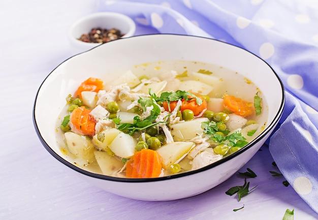 Sopa de pollo con guisantes verdes, zanahorias y papas en un tazón blanco Foto gratis