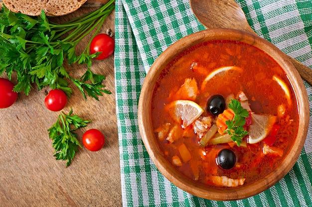 Sopa rusa solyanka con carne, aceitunas y pepinillos en un tazón de madera Foto gratis