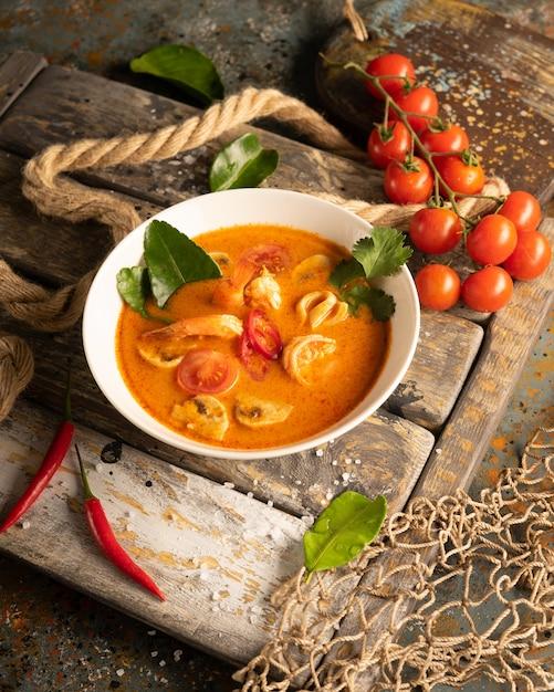 Sopa tom yam con camarones, calamares y pimientos picantes en una tabla de madera con textura Foto Premium