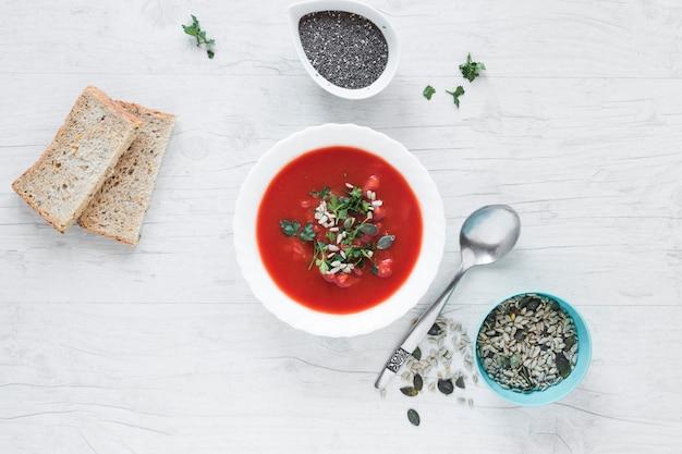 Sopa de tomate con chia y semillas de calabaza con una rebanada de pan en una mesa de madera blanca Foto gratis
