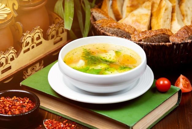 Sopa de verduras casera de pollo, vista desde arriba sobre un libro sobre la mesa Foto gratis