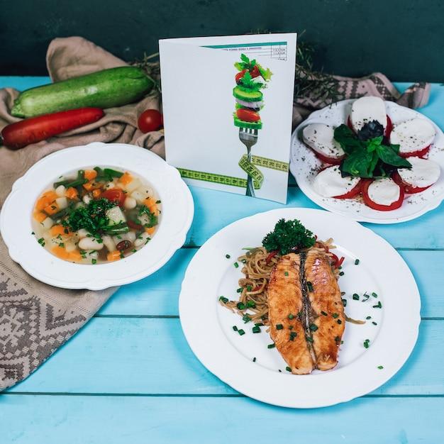 Sopa de verduras, filete de pescado a la parrilla y ensalada de mozarella en la mesa de madera azul. Foto gratis