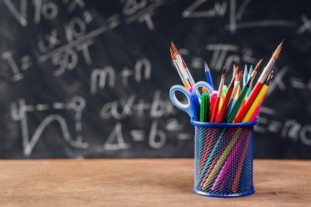 Soporte para lápiz azul con herramientas de dibujo colocadas en el escritorio Foto gratis