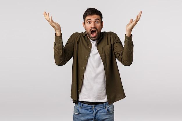 Sorprendido y avergonzado, un hombre barbudo entrando en pánico, levantando las manos de lado, perplejo y confundido, sintiéndose frustrado y sin palabras, jadeando, mirando a cámara con problemas, enfrentado a una situación extraña Foto Premium