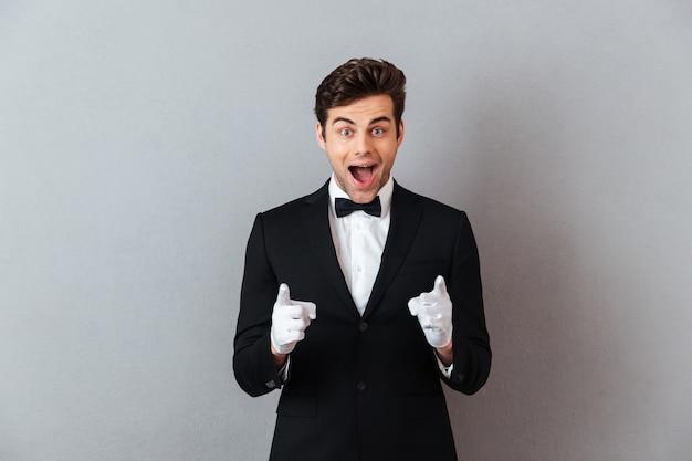 Sorprendido feliz joven camarero apuntando a usted. Foto gratis
