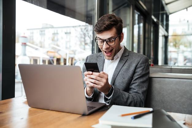 Sorprendido hombre de negocios feliz en anteojos sentado junto a la mesa de café con computadora portátil y uso de teléfono inteligente Foto gratis