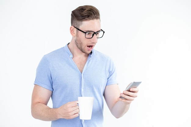 Sorprendido joven en gafas con teléfono inteligente Foto gratis