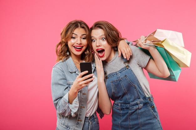 Sorprendió a dos amigas sosteniendo bolsas de compras usando el teléfono móvil. Foto gratis