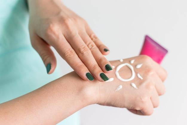 Sosteniendo la botella de protector solar con crema como forma de sol en la mano Foto Premium