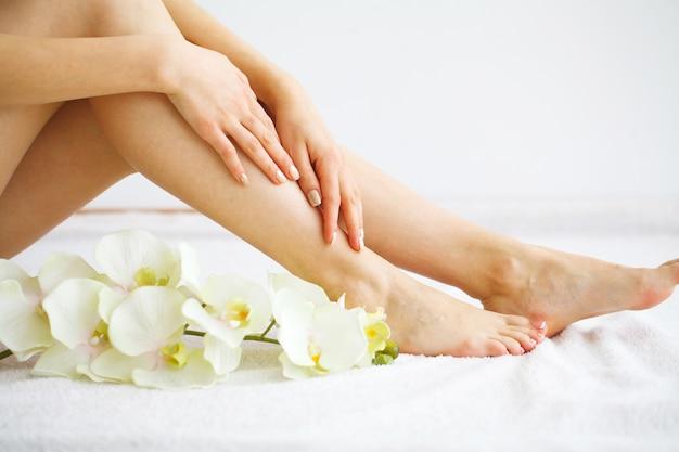 Spa. mujer masajeando piernas sentado Foto Premium