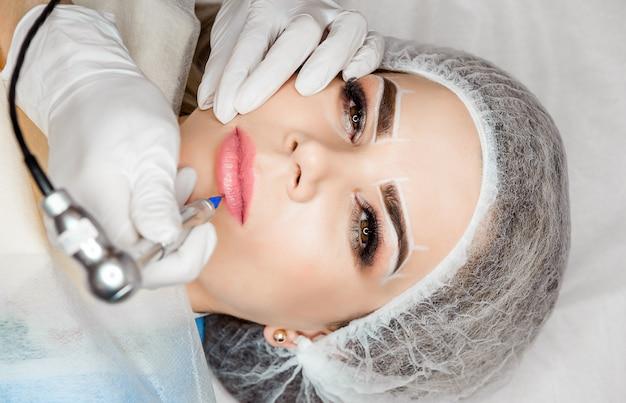 Spa saludable. mujer hermosa joven que tiene tatuaje permanente del maquillaje en sus labios Foto Premium