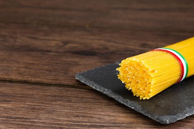 Spaghetti en pizarra con fondo de madera Foto gratis