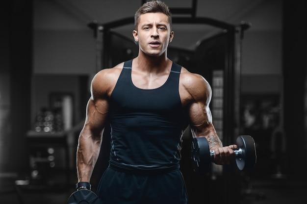 Sport fitness muscular hombre trabajando en el gimnasio Foto Premium