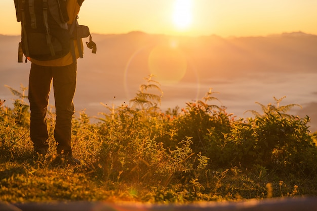 Stand de excursionista en el camping cerca de la carpa naranja y mochila en las montañas Foto gratis