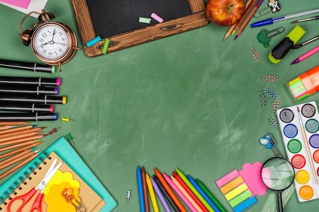 Statonery de la escuela en pizarra verde Foto Premium