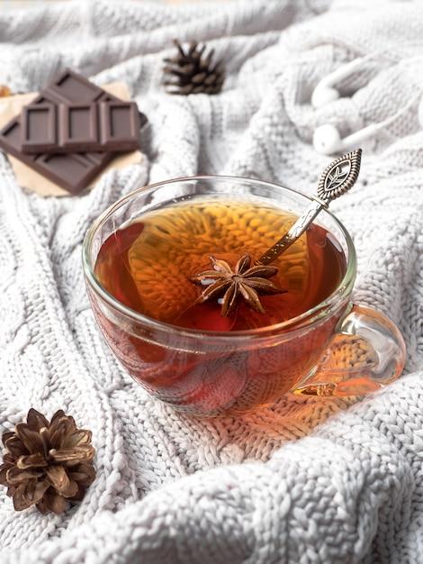 Suéter de punto cálido, una taza de té caliente con chocolate y decoraciones de invierno. Foto Premium