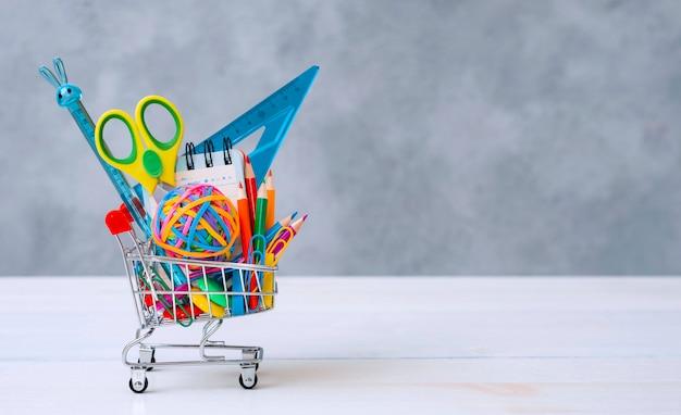 Suministros escolares multicolores en un carrito de compras sobre un fondo gris con espacio de copia de texto. el concepto de regresar a la escuela para el nuevo año escolar, compras. Foto gratis