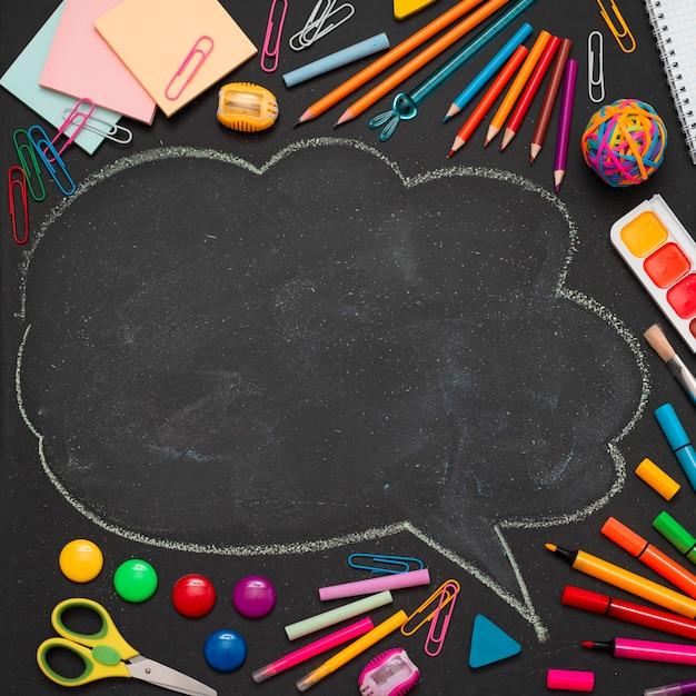 Suministros escolares multicolores, lápices y una nube dibujada con espacio para copiar texto. Foto gratis