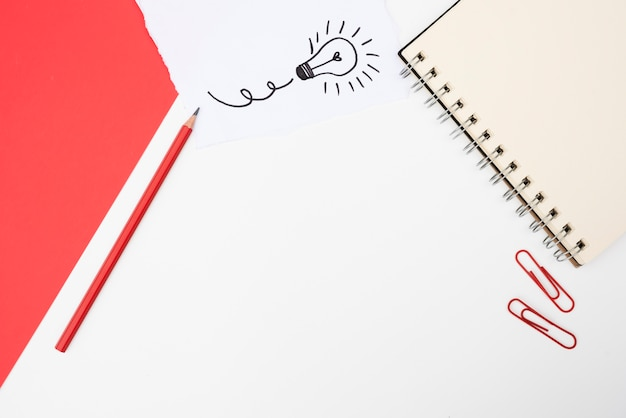 Suministros de oficina y papel blanco con bombilla dibujada a mano sobre superficie blanca Foto gratis
