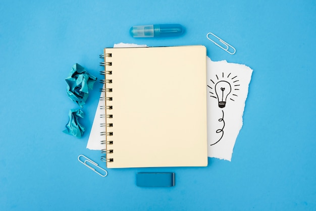 Suministros de papelería y espiral en blanco con bombilla dibujada a mano sobre papel blanco sobre superficie azul Foto Premium