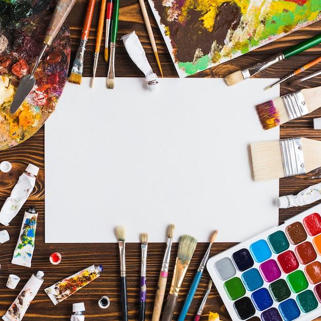 Suministros de pintura en la mesa alrededor de papel Foto gratis