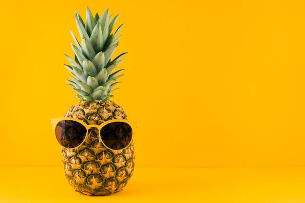 Sunglass en piña contra fondo amarillo Foto Premium