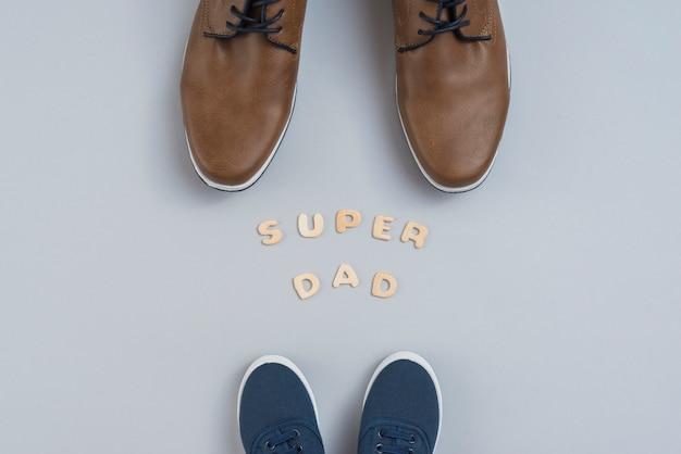 Súper papá inscripción con zapatos de hombre y niños. Foto gratis