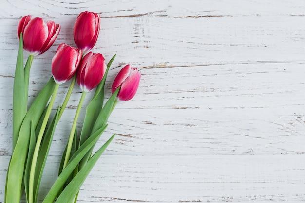 Superficie de madera blanca con tulipanes para el día de la madre Foto gratis