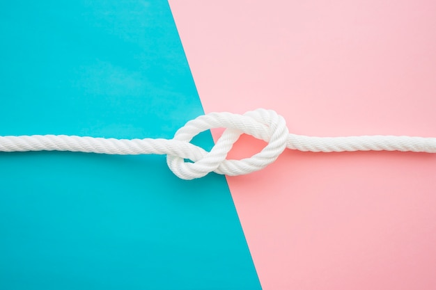 Superficie rosa y azul con nudo marino Foto gratis
