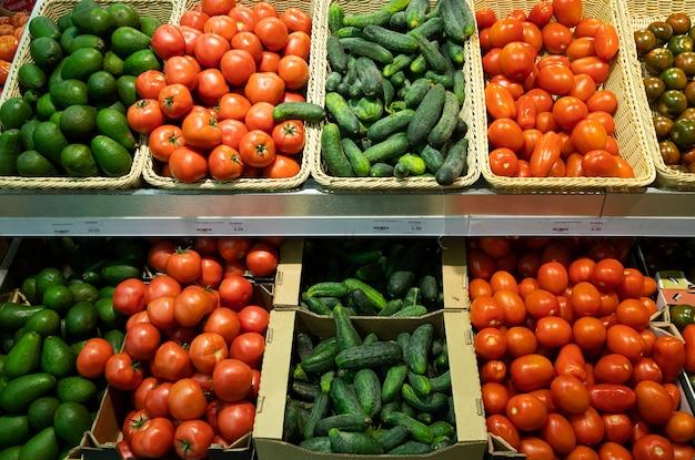 Supermercado con cestas de mimbre y cajas con tomates, pepinos y aguacates. Foto Premium