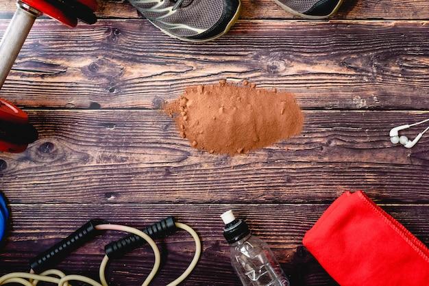 Suplemento deportivo a base de suero, proteínas y carbohidratos con sabor a cacao, fondo con accesorios de fitness. Foto Premium