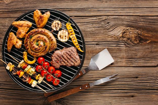 Surtido de carnes marinadas y salchichas a la parrilla en una parrilla de barbacoa sobre fondo de madera Foto gratis