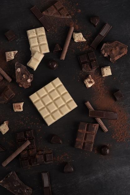 Surtido de diferentes tipos de barras de chocolate en pedazos Foto gratis