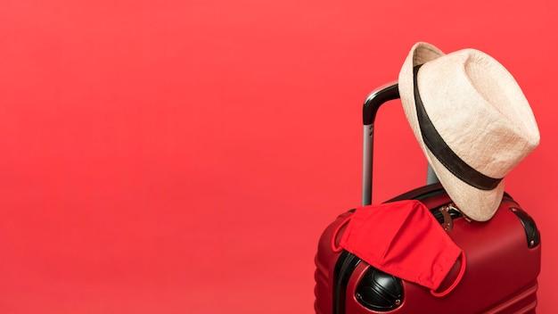 Surtido con equipaje y fondo rojo. Foto gratis