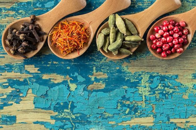 Surtido de especias coloridas en cucharas de madera. Foto Premium