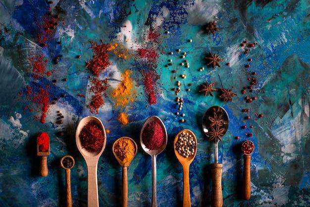 Surtido de especias naturales en cucharas vintage sobre hormigón azul Foto Premium