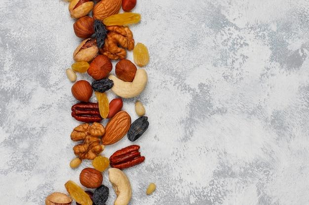 Surtido de frutos secos en platos de cerámica. anacardo, avellanas, nueces, pistacho, nueces, piñones, maní, pasas vista superior. Foto gratis