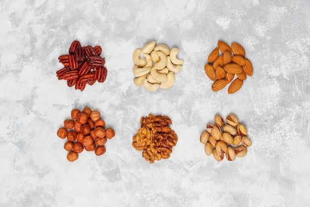 Surtido de nueces anacardos, avellanas, nueces, pistachos, nueces, piñones, maní, pasas. vista superior Foto gratis