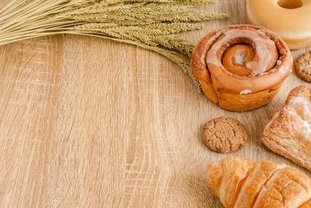 Surtido de panes recién horneados, pasteles, croissant y trigo en la superficie de la mesa de madera Foto Premium
