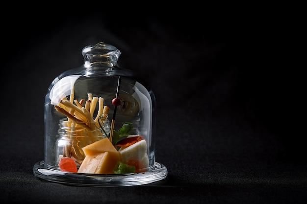 Surtido de quesos con bayas y mermelada, mini servir en un matraz de vidrio. concepto de comida fusión, bajo perfil, copia espacio. Foto Premium