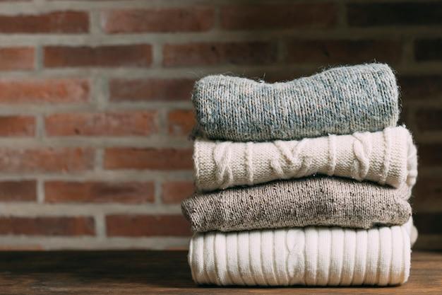 Surtido con ropa abrigada y pared de ladrillo. Foto gratis