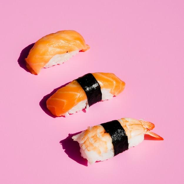 Sushi de salmón y camarones sobre fondo rosa Foto gratis