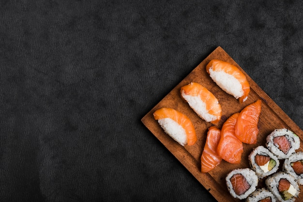 Sushi y salmón rebanadas en tabla de cortar de madera sobre el fondo negro Foto gratis