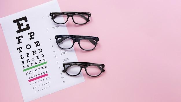 Tabla del alfabeto con gafas sobre fondo rosa Foto Premium