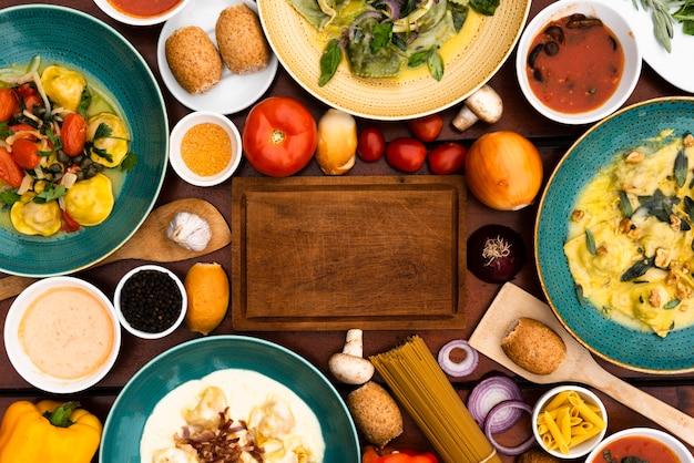 Tabla de cortar de madera rodeada de platos de pasta e ingredientes en la mesa Foto gratis
