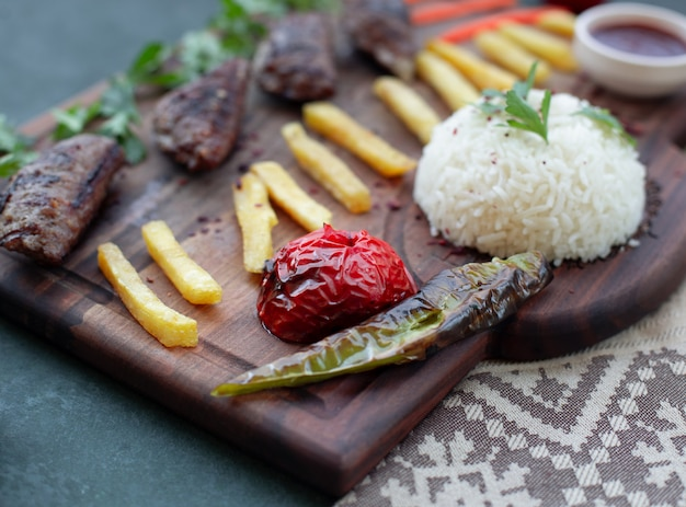 Tabla de kebab con fuegos franceses, comidas a la parrilla y arroz. Foto gratis
